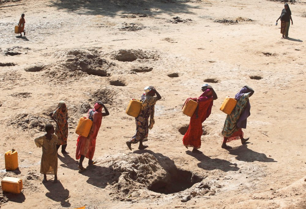 Women carry jerry cans of water from shallow wells dug from the sand along the Shabelle River bed, which is dry due to drought in Somalia's Shabelle region